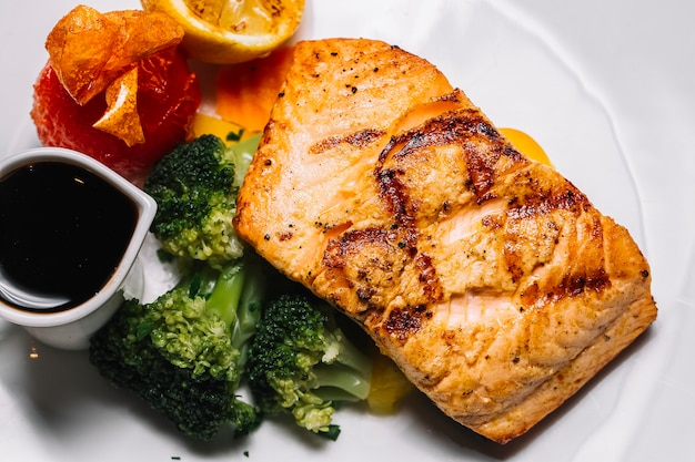 Vista superior grelhada posta de peixe vermelha com brócolis, uma fatia de limão tomate e molho narsharab Foto gratuita