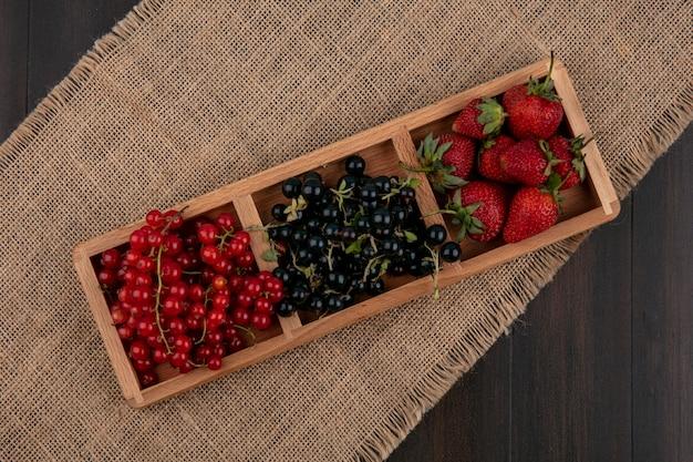 Vista superior groselha vermelha e preta com morangos em um fundo de madeira Foto gratuita
