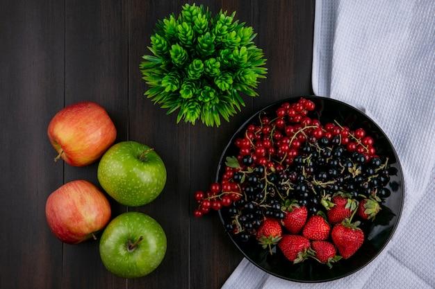 Vista superior groselha vermelha e preta com morangos em um prato com maçãs em um fundo de madeira Foto gratuita
