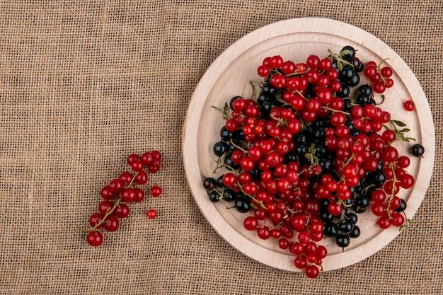 Vista superior groselha vermelha e preta em um prato em um guardanapo bege Foto gratuita