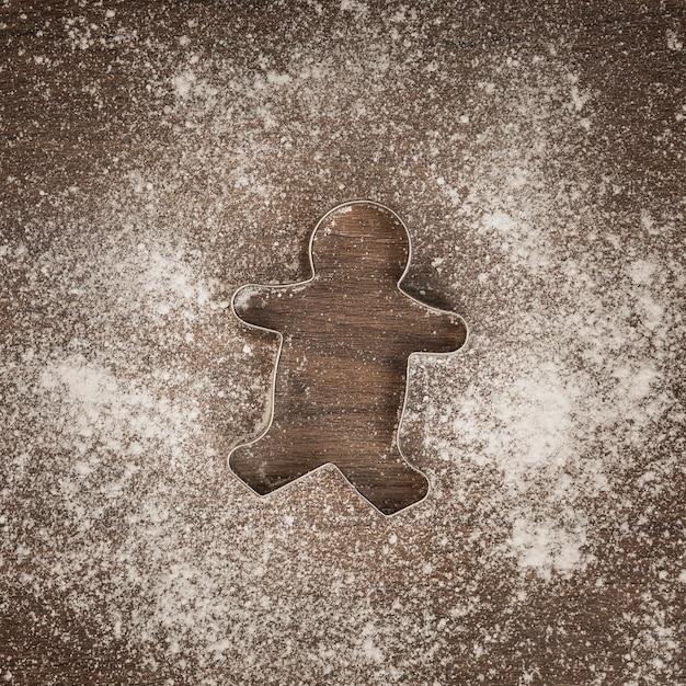 Vista superior homem-biscoito cortador de biscoitos com farinha Foto gratuita