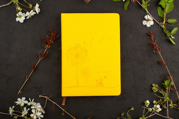 Vista superior, imagem amarela, juntamente com flores no chão escuro Foto gratuita