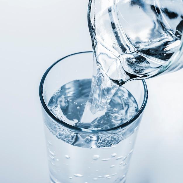 Vista superior jarra de enchimento de copo de água Foto gratuita