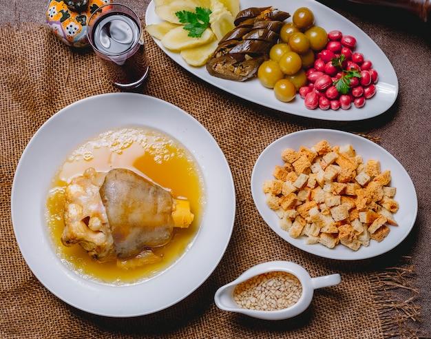 Vista superior khash com berinjela em conserva dogwood pepino cereja ameixa pão rusk vinagre e alho Foto gratuita