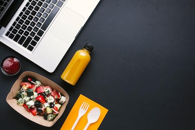 Vista superior laptop e salada em fundo preto Foto gratuita