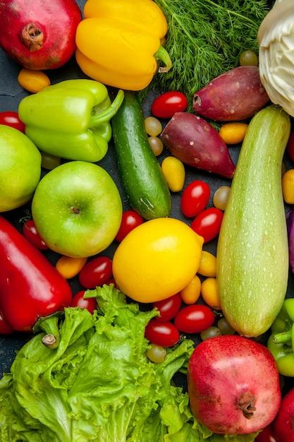 Vista superior legumes e frutas abobrinha pimentões tomates cereja cumcuat repolho limão romãs kiwi alface pepino Foto gratuita