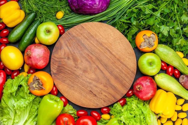 Vista superior legumes e frutas alface tomate pepino endro tomate cereja abobrinha cebola verde salsa romã caqui maçã mesa redonda de madeira no centro Foto gratuita
