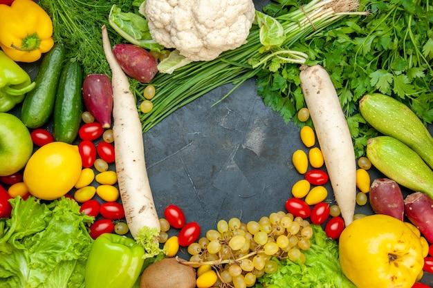 Vista superior legumes e frutas tomates cereja cumcuat alface marmelo uva limão couve-flor rabanete branco salsa abobrinha pepinos espaço livre no centro Foto gratuita