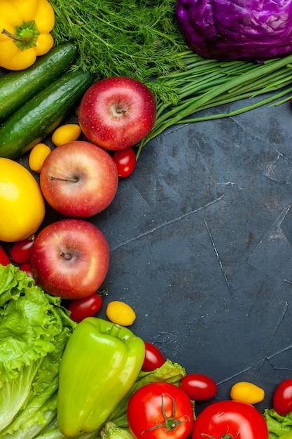 Vista superior legumes e frutas tomates cereja maçãs cumcuat pepinos repolho roxo pimentão espaço livre Foto gratuita