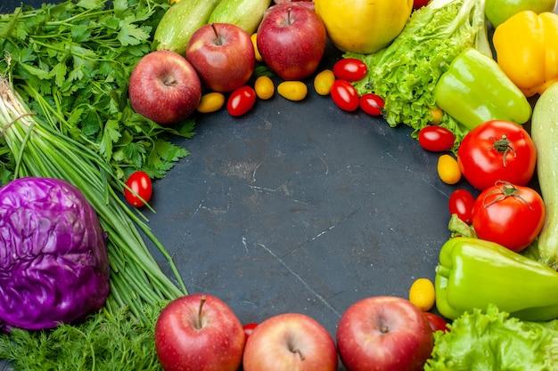 Vista superior legumes e frutas tomates cereja maçãs cumcuat repolho roxo cebola verde alface salsa pimentões com espaço livre Foto gratuita