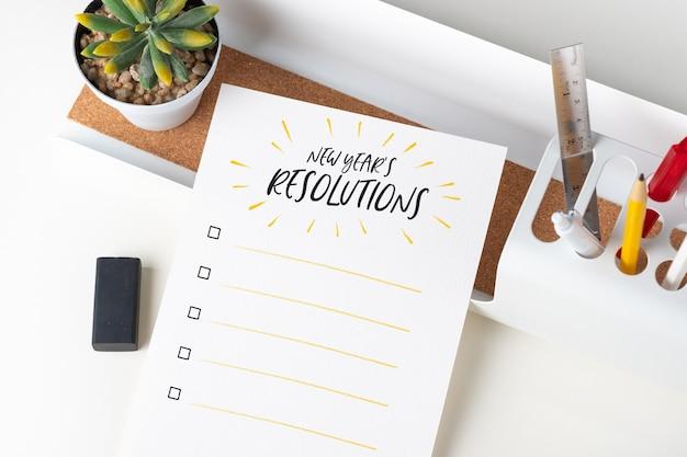 Vista superior lista de verificação de resoluções de ano novo em papel branco nota no escritório moderno Foto Premium