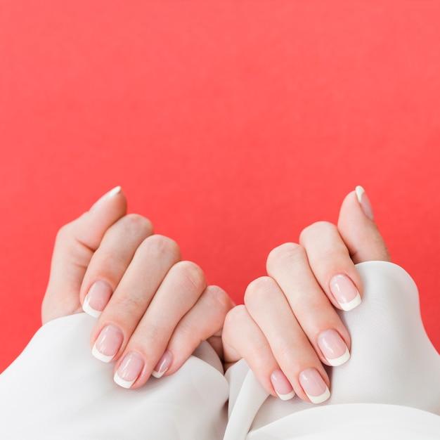 Vista superior manicured mãos no fundo rosa vibrante Foto Premium