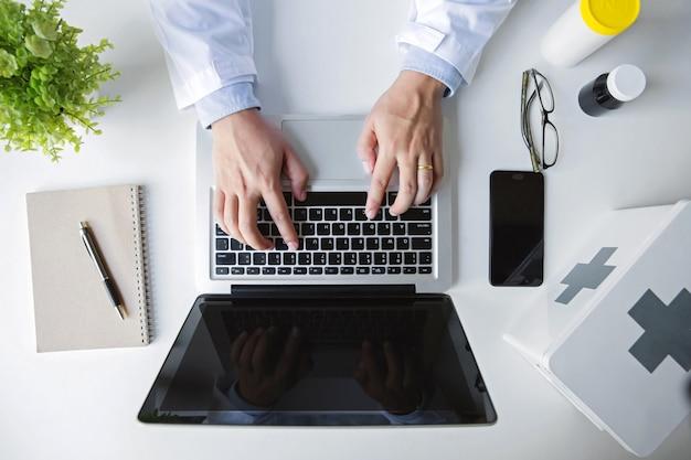 Vista superior. mão de médico trabalhando com o computador portátil no escritório da área de trabalho médica como conceito Foto Premium
