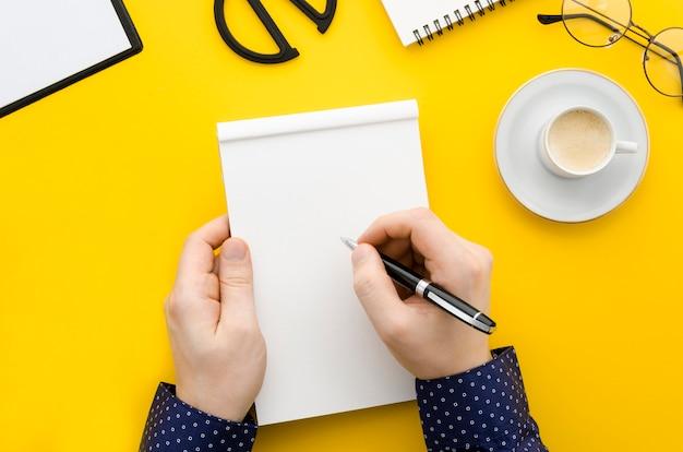 Vista superior mão escrevendo no caderno Foto gratuita