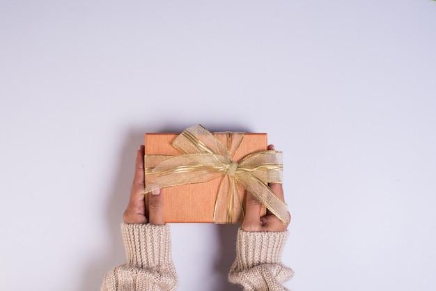 Vista superior mão segurando a caixa de presente no espaço de trabalho Foto gratuita