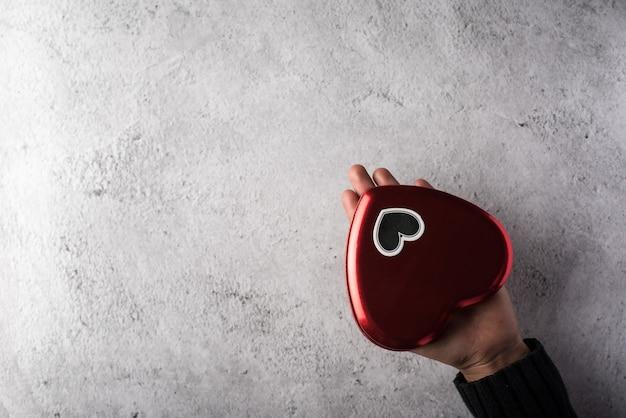 Vista superior mão segurando coração vermelho no fundo da parede Foto gratuita