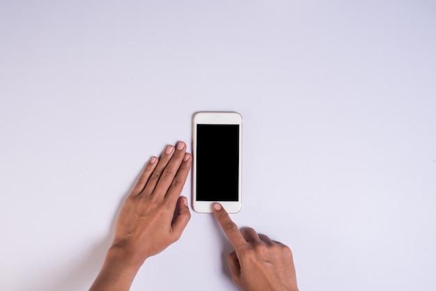 Vista superior, mão, segurando, telefone pilha, branco, fundo Foto gratuita
