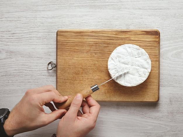 Vista superior, mãos de homem bonito e brutal cortam com precisão um pedaço triangular de queijo camembert com Foto gratuita