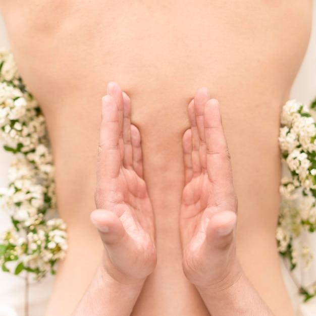 Vista superior mãos massageando as costas Foto gratuita