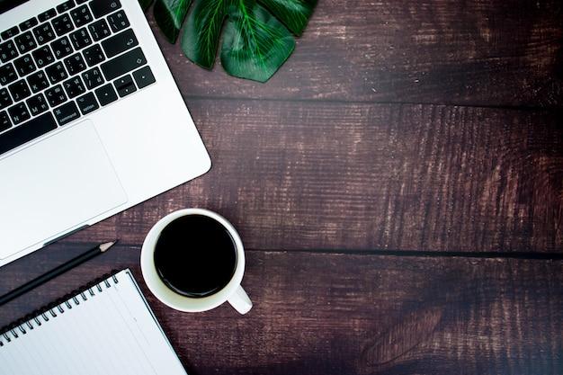 Vista superior mesa de madeira mesa com laptop, café, caneta, folhas com espaço de cópia. Foto Premium