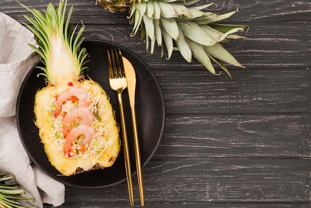Vista superior metades de abacaxi com talheres Foto gratuita