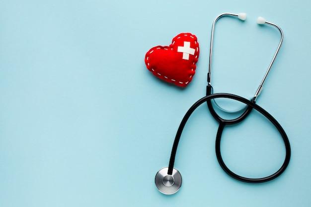 Vista superior minimalista coração vermelho com estetoscópio Foto gratuita