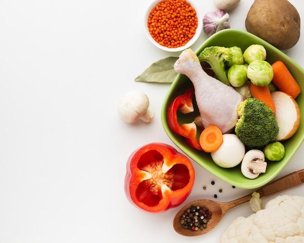 Vista superior mistura de legumes na tigela e coxa de frango com espaço de cópia Foto gratuita