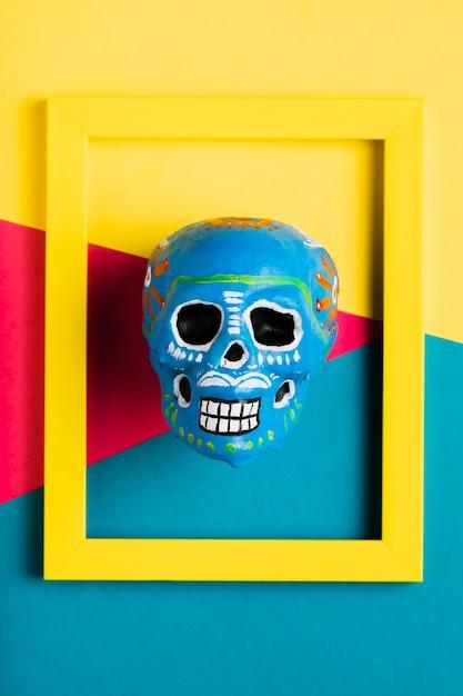 Vista superior moldura amarela com caveira azul Foto gratuita