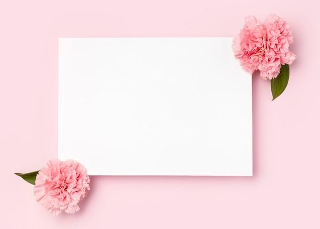 Vista superior moldura branca rodeada de flores Foto Premium