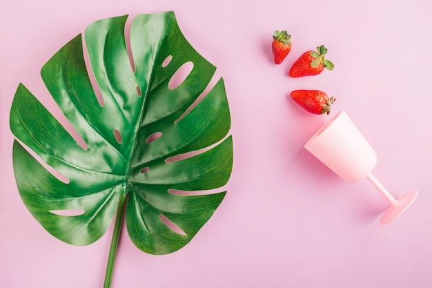 Vista superior, morangos, copo e folha Foto gratuita