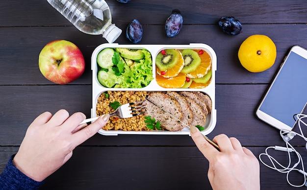 Vista superior, mostrando as mãos a almoçar saudável com bulgur, carne e legumes frescos e frutas em uma mesa de madeira. fitness e conceito de estilo de vida saudável. lancheira. vista do topo Foto gratuita