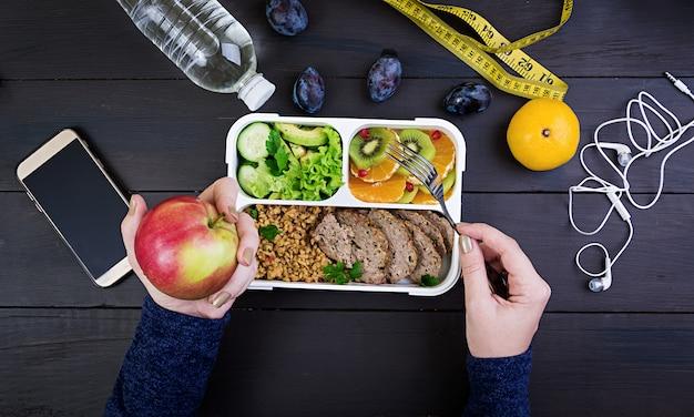 Vista superior, mostrando, mãos, comendo saudável, almoço, com, bulgur, carne, e, legumes frescos, e, fruta Foto Premium