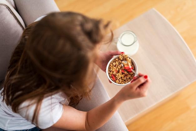Vista superior mulher comendo cereais Foto gratuita