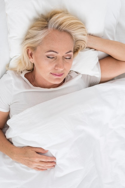 Vista superior mulher feliz dormindo Foto gratuita