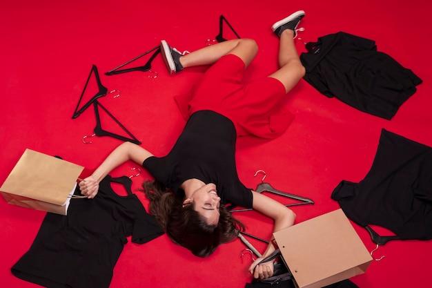 Vista superior mulher ficar no chão com suas roupas novas Foto gratuita
