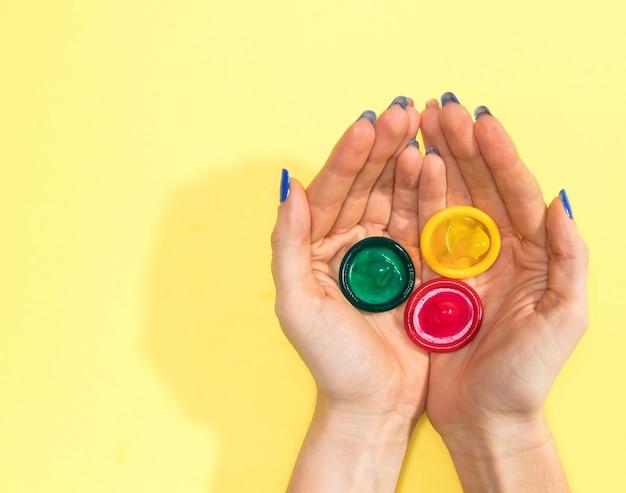 Vista superior, mulher, segurando, três, preservativos Foto gratuita