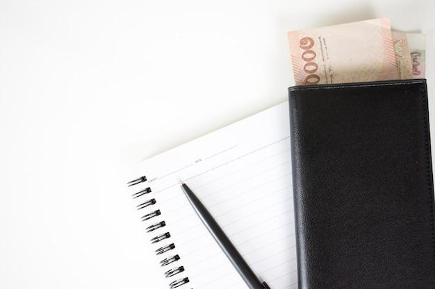 Vista superior note book com caneta e dinheiro no bolso em uma mesa branca com espaço de cópia. Foto Premium