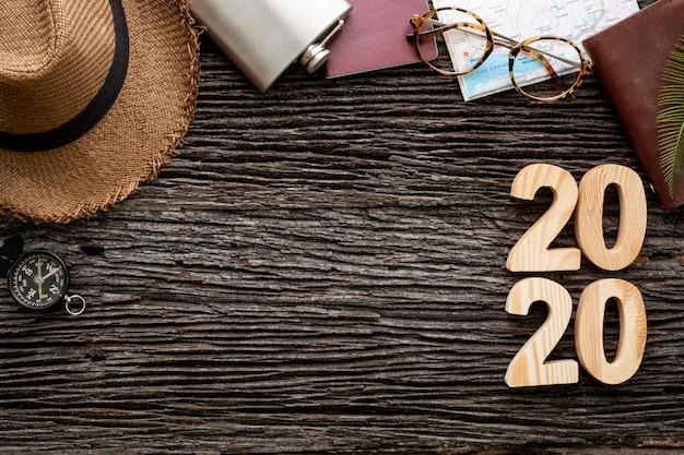 Vista superior número de feliz ano novo de 2020 na mesa de madeira com item de acessório de aventura Foto Premium