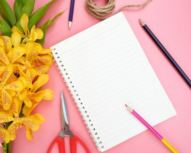 Vista superior ou configuração lisa do papel aberto do caderno, flores amarelas da orquídea, lápis da cor, tesouras e corda da natureza no fundo cor-de-rosa. Foto Premium