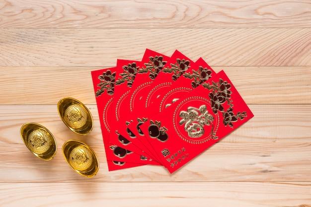 Vista superior ouro e vermelho ano novo chinês decoração em fundo de madeira Foto Premium
