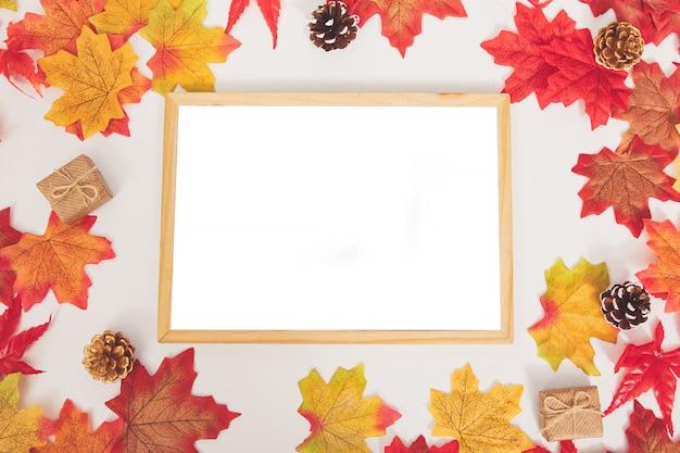 Vista superior outono colorido maple folhas, cones, caixa de presente e moldura de superfície de madeira em branco Foto Premium
