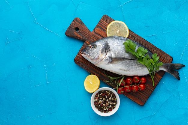 Vista superior peixe no fundo de madeira com condimentos Foto gratuita