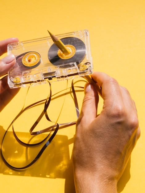 Vista superior pessoa reparar fita cassete com lápis Foto gratuita