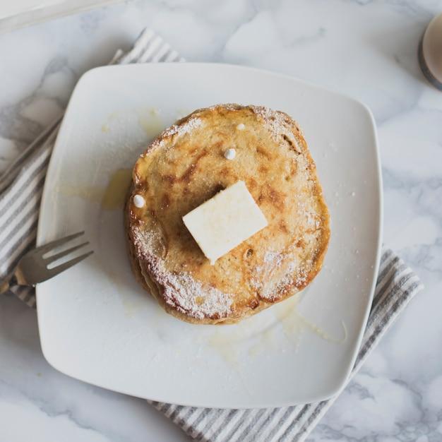 Vista superior pilha de panquecas com manteiga Foto gratuita