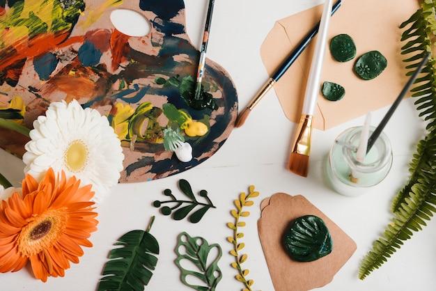 Vista superior pintura materiais e ferramentas na mesa Foto gratuita