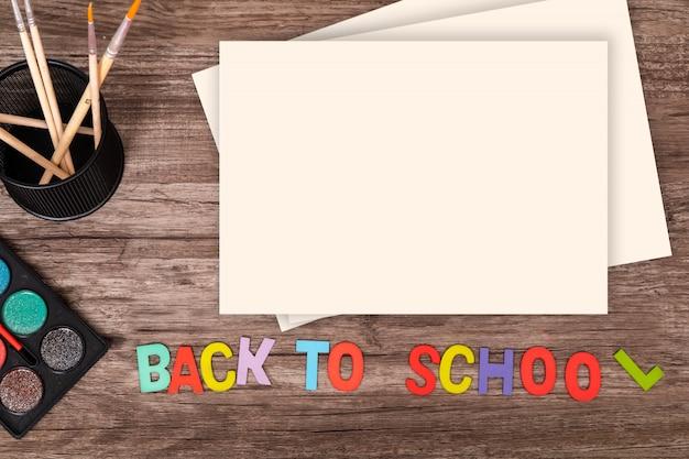 Vista superior plana colocar as mãos do menino tocar o alfabeto de volta à escola em fundo de madeira com espaço de cópia Foto Premium