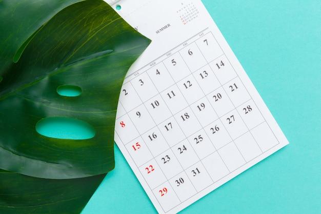 Vista superior plana leiga de mesa de espaço de trabalho estilo material de escritório com calendário Foto Premium