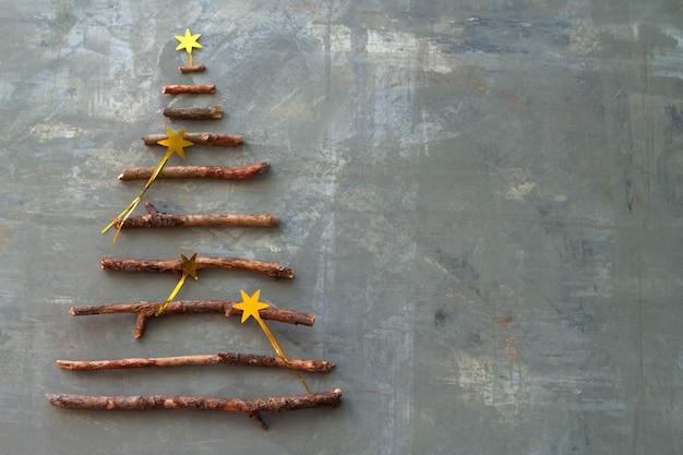 Vista superior plana leigos silhueta de uma árvore de natal feita de galhos de madeira decorados com estrelas douradas Foto Premium