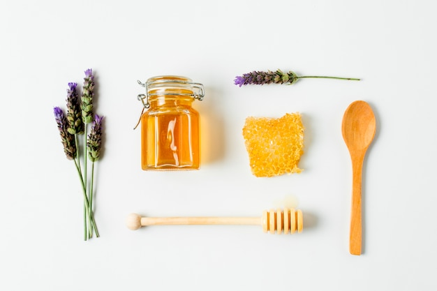 Vista superior pote de mel com lavanda e colheres Foto gratuita