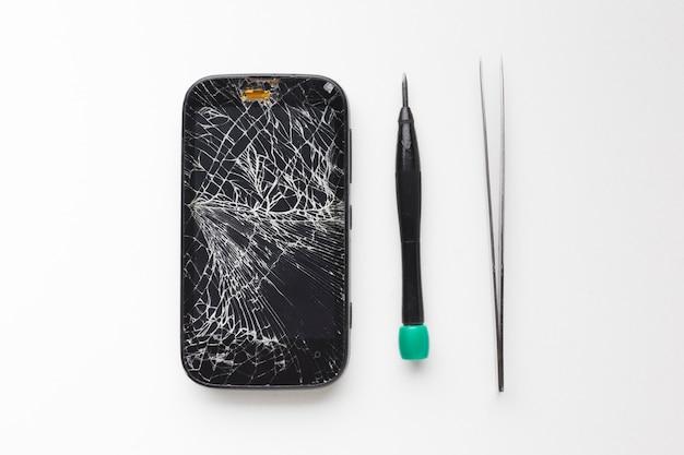 Vista superior quebrado smartphone com ferramentas de reparo Foto gratuita